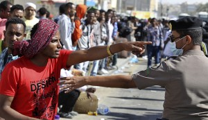 An Ethiopian worker argues with Saudi security forces while waiting for repatriation in Manfouha